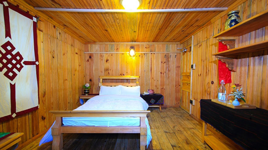 Cozy wood finished room with comfortable bed and warm lighting